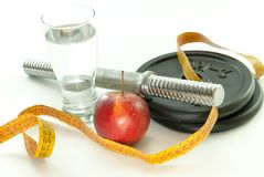 Glass of water green apple dumbbells and measuring tape concept photo of weight loss workout exercise and healthy life. Glass of water red apple dumbbells and Stock Image