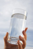 Glass of water in hand. Glass of water in women hand against the blue sky Stock Photos