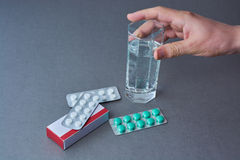 A glass of water in a hand and a pack of tablets on a table. Stock Photos