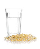 Glass with water and a heap of tablets, pills Royalty Free Stock Photos