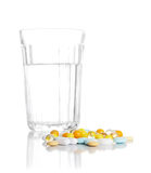 Glass with water and a heap of tablets, pills Stock Photos