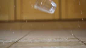 Dringing glass hitting the ground. Glass of water hitting the ground shattering and splashing on the kitchen floor, slow motion 120 FPS capture stock footage