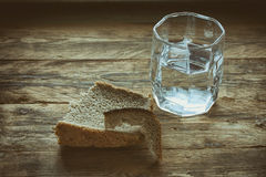 Glass of water and hunk black bread. Crust on old wooden table, concept hunger need Royalty Free Stock Photos