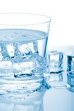 Glass of water with ice. Glass of fresh water with cubes of ice in it over paper background royalty free stock images