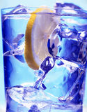 Glass with water and ice. On the blue background Royalty Free Stock Photos