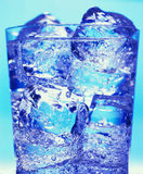 Glass with water and ice. On the blue background Royalty Free Stock Photography
