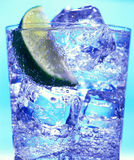 Glass with water and ice. On the blue background Royalty Free Stock Image