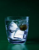 Glass with water and ice. On the green background Royalty Free Illustration