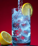 Glass with water and ice. On the red background Royalty Free Stock Images