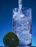 Glass with water and ice. On the blue background Stock Photography