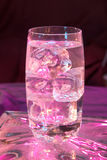 Glass of water with ice. Lit by purple light stock image