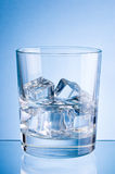 Glass of water with ice on blue background Royalty Free Stock Photo