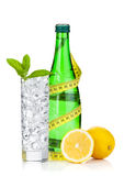 Glass of water with ice, bottle, measuring tape, lemon and mint Stock Image