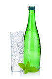 Glass of water with ice, bottle and mint Stock Photography