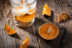 Glass of water with ice cubes and dried orange Stock Photos