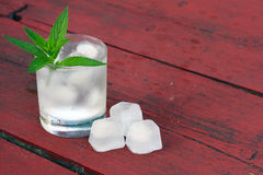 Glass of water with ice cubes and mint on wooden table Stock Images