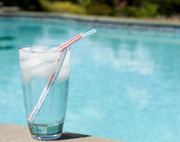 Glass of water with ice cubes on side of pool Stock Photography