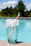 Glass of water with ice cubes on side of pool Royalty Free Stock Image