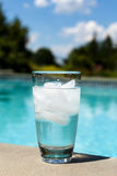 Glass of water with ice cubes on side of pool Stock Photos