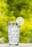 Glass of water and Ice with Lime placed outdoors Stock Photos