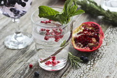 Glass of water with ice, mint and pomegranate seeds on a wooden Stock Photo
