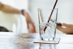Glass of water and ice on a table in restaurant background Stock Image