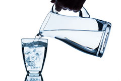 Glass with water and jug. Pure water is emptied into a glass of water from a jug. fresh drinking water Stock Images