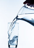Glass with water and jug Stock Images