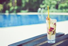 A glass of water juice on swimming pool in vacation and summer time. Royalty Free Stock Photos