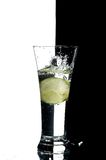 Glass with water and lemon. On the white and black background Royalty Free Stock Photography