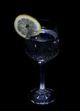 Glass with water and lemon on a black background Royalty Free Stock Images