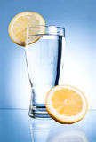Glass of water and lemon on a blue Stock Photography