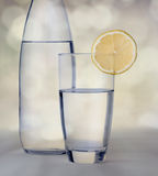 Glass of water with lemon in front of water bottle with bokeh ba. Ckground royalty free stock images