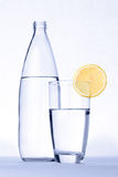 Glass of water with lemon in front of water bottle isolated on w. Hite royalty free stock photography