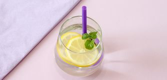 Glass of water, lemon and mint. Glass of pure water, fresh organic lemon and mint  on purple background. Detox. And healthy food concept. Boost your metabolism Royalty Free Stock Photo