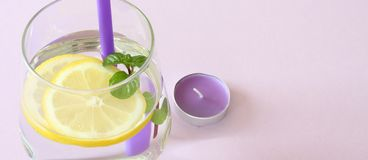 Glass of water, lemon and mint. Glass of pure water, fresh organic lemon and mint  on purple background. Detox. And healthy food concept. Boost your metabolism Stock Images