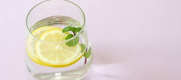 Glass of water, lemon and mint. Glass of pure water, fresh organic lemon and mint  on purple background. Detox. And healthy food concept. Boost your metabolism Stock Image