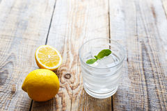 Glass of water with lemon and mint on wooden table Stock Photo