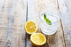 Glass of water with lemon and mint on wooden table Stock Photography