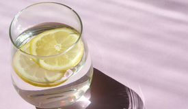 Glass of water and lemon. Glass of pure water and fresh organic lemon  on purple background. Detox and healthy food. Glass of water and lemon. Glass of pure Royalty Free Stock Photos