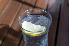 Glass of water with lemon slice and ice cube on the table. Glass of water with lemon slice and ice cube on the wooden table Royalty Free Stock Photography