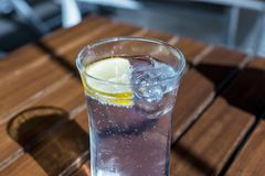 Glass of water with lemon slice and ice cube on the table. Glass of water with lemon slice and ice cube on the wooden table Royalty Free Stock Image