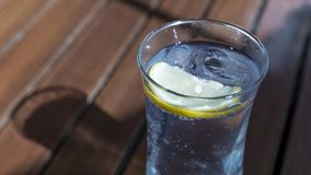 Glass of water with lemon slice and ice cube on the table. Glass of water with lemon slice and ice cube on the wooden table Royalty Free Stock Images