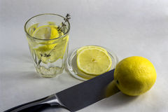 Glass with water and lemon. Still life from the knifed lemon and a glass with lemon water Stock Photo