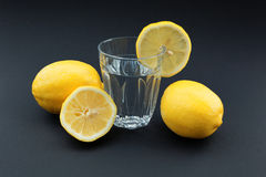 Glass of water with lemon surrounded by lemons Stock Image