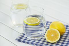 Glass of water with lemon on white background Royalty Free Stock Photo