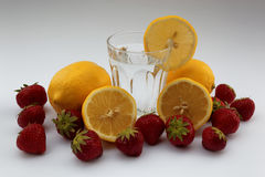 Glass of water with lemons and strawberries Stock Images