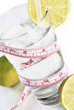 Glass of water, limes & tape measure Royalty Free Stock Photos