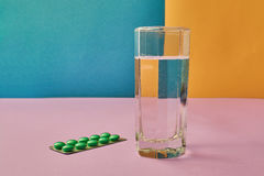 The Glass of water and medicine capsule. The Glass of water and pill from the package Stock Images