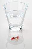 Glass of Water and Medicine Capsules Stock Photos
